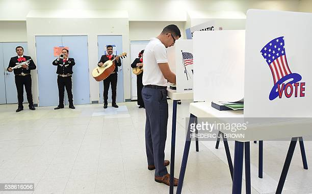TOPSHOT First time voter Victor Rodriguez is serenaded by a Mariachi band while casting his vote at a polling station in Cudahy California on June 7...