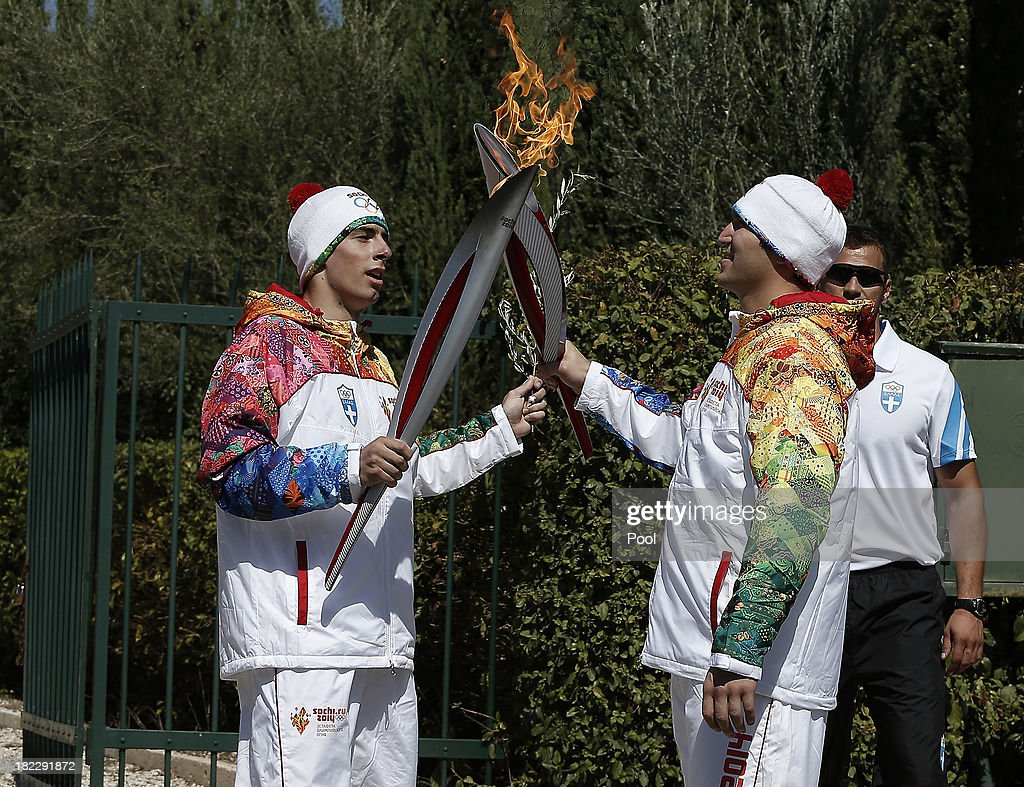 First torchbearer Yiannis Antoniou relays the flame to second torchbearer Alexander Ovechkin of Russia outside the Pierre de Coubertin monument during the torch relay September 29, 2013 in Olympia, Greece. After the lighting ceremony of the Olympic flame at Ancient Olympia, in west southern Greece, the torch will the be relayed to the Russian resort of Sochi, which will host the Winter Olympics on February, 2014