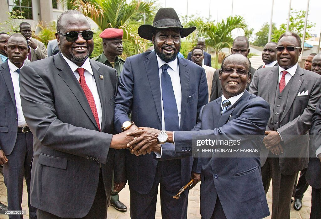 First Vice President of South Sudan and former rebel leader Riek Machar, South Sudan President Salva Kiir and Second Vice President of South Sudan James Wani Igga shake hands after the formation of the new cabinet of the Transitional Government at the Cabinet Affairs Ministry in Juba on April 29, 2016. South Sudan President Salva Kiir has named his transitional unity government, sharing power with ex-rebels in a key step in a long-delayed peace process, a decree read out on April 29 said. Under terms of an August 2015 peace deal, the 30 ministerial posts are split between Kiir, former rebel chief turned first vice president Riek Machar, opposition and other parties. FARRAN