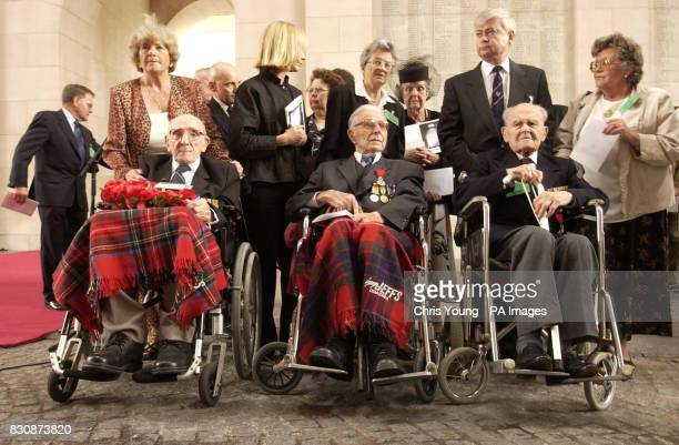 First World War veterans from left Jack Davis Harry Patch and Arthur Halestrap sit with unidentified family members at The Menin Gate Ypres Belgium...