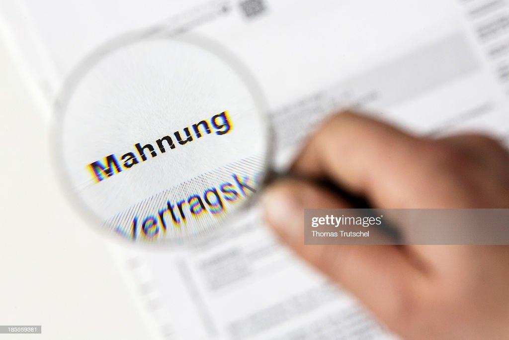 First written demand. Close-up of a written reminder photographed through a magnifying glass.
