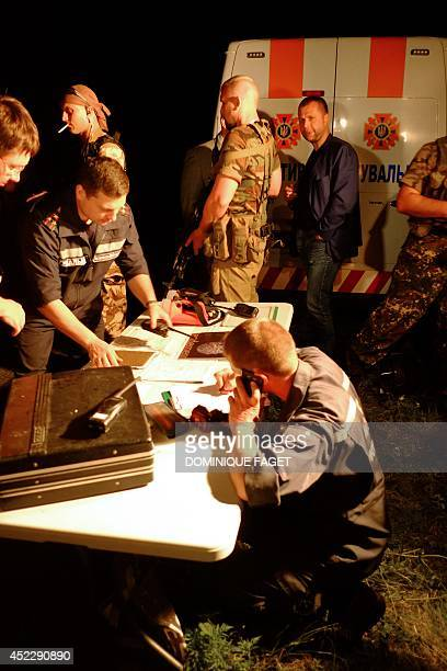 Firstaid workers and selfproclaimed Prime Minister of the proRussian separatist 'Donetsk People's Republic' Alexander Borodai gather on July 17 2014...