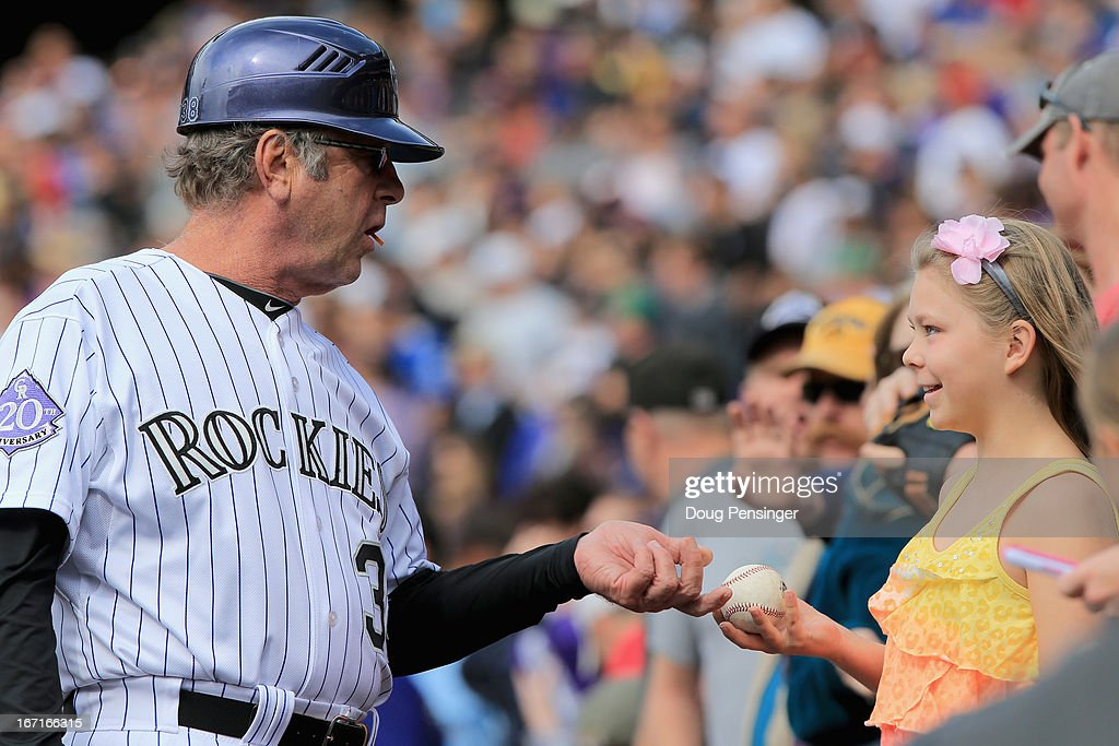 Firstbase coach <a gi-track='captionPersonalityLinkClicked' href=/galleries/search?phrase=Rene+Lachemann&family=editorial&specificpeople=588067 ng-click='$event.stopPropagation()'>Rene Lachemann</a> #38 of the Colorado Rockies gives a ball to a young fan at Coors Field on April 21, 2013 in Denver, Colorado. The Diamondbacks defeated the Rockies 5-4.