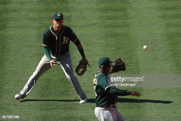 Firstbaseman Ryon Healy of the Oakland Athletics tosses the ball to relief pitcher Santiago Casilla for the third out of the eighth inning with the...