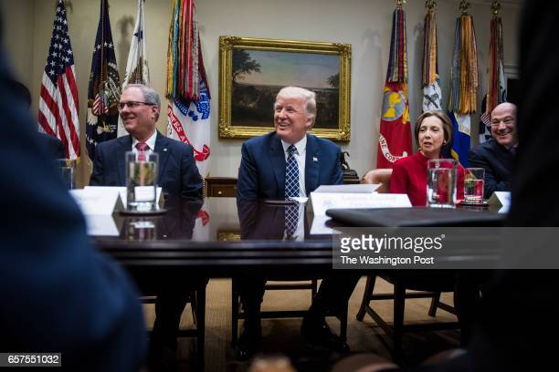 FirstCapital Bank of Texas Chairman Kenneth Burgess Jr left President Donald Trump and Cape Cod Five Cents Savings Bank CEO Dorothy Savarese listen...