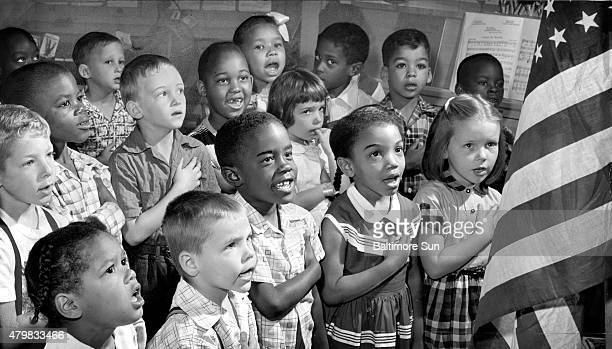 Firstgrade students at Public School 60 in Baltimore say the Pledge of Allegiance to the American flag in June 1955