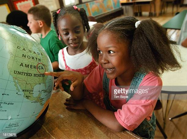 Firstgrader Khatona Miller right investigates a circled location on a world globe with other classmates August 22 2000 at Chicago's Stewart...