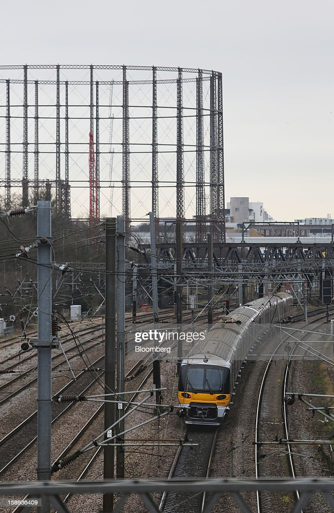 A FirstGroup Plc train passes the supporting structure of a gas storage tank, left, before arriving at Paddington railway station in London, U.K., on Thursday, Jan. 3 2013. Rail commuters have been hit by inflation busting fare increases of up to 10 per cent, adding hundreds of pounds to the cost of annual season tickets. Photographer: Chris Ratcliffe/Bloomberg via Getty Images
