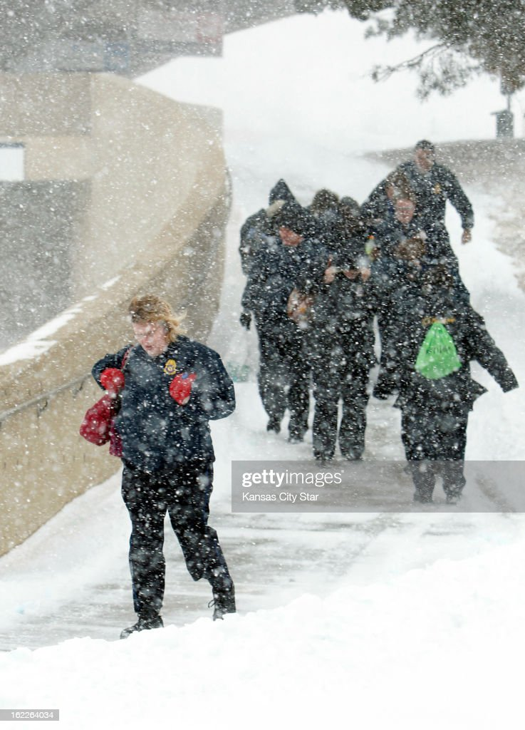 Firstline security personnel fight the cold, wind and snow as they leave Kansas City International Airport after it closed due to heavy snow, Thursday morning, February 21, 2013.