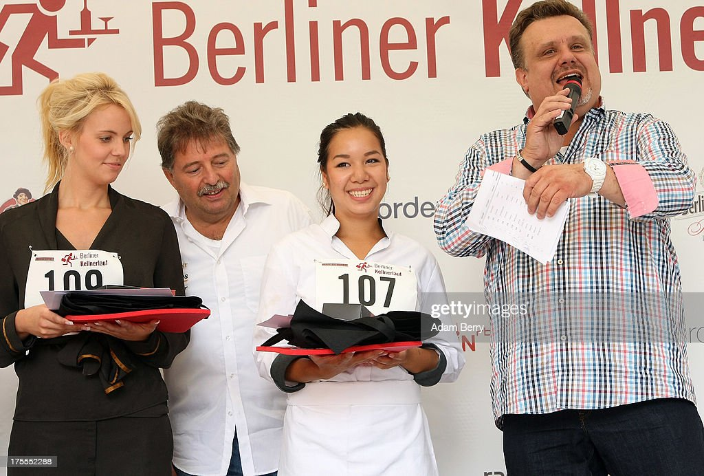 First-place winning waitress Anh Susan Pham Thi (3 from L) and second-place winning waitress Natalie Behrendt (L) stand on the stage while receiving their prizes during the Waiters' Derby (Kellner Derby in German) on August 4, 2013 in Berlin, Germany. At the annual event, brought back into existence in 2011 on the 125th anniversary of the Kurfuerstendamm (known locally as the Ku'damm), a main shopping thoroughfare, waiters, porters, cooks and bartenders run a 400-meter track while performing their regular occupational duties. The event was reinstated after a hiatus since the 1950s, when it was created to bring a sense of normal life back to Berlin after World War II under the Allies, a period in which gastronomical interest in the isolated Western part of the city suffered.