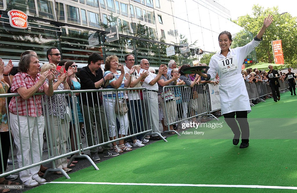 First-place winning waitress Anh Susan Pham Thi celebrates as she crosses the finish line during the Waiters' Derby (Kellner Derby in German) on August 4, 2013 in Berlin, Germany. At the annual event, brought back into existence in 2011 on the 125th anniversary of the Kurfuerstendamm (known locally as the Ku'damm), a main shopping thoroughfare, waiters, porters, cooks and bartenders run a 400-meter track while performing their regular occupational duties. The event was reinstated after a hiatus since the 1950s, when it was created to bring a sense of normal life back to Berlin after World War II under the Allies, a period in which gastronomical interest in the isolated Western part of the city suffered.