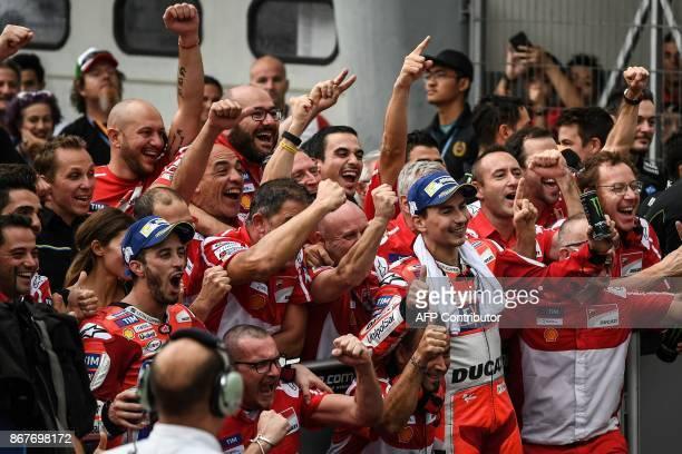 TOPSHOT Firstplaced Ducati Team's Italian rider Andrea Dovizioso and secondplaced Ducati Team's Spanish rider Jorge Lorenzo celebrate with teammates...