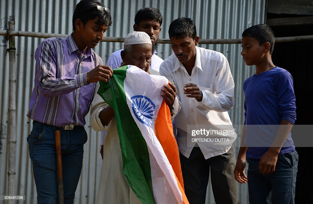 First-time Indian voter Asgar Ali (C), 103, is given a national flag before casting his ballot in the state assembly elections at a polling station in Cooch Behar district on May 5, 2016. Frail, aided by his grandson and beaming with pride, 103-year-old Asgar Ali was among thousands who cast their ballots for the first time in elections held in eastern India on May 5. Caught in one of the world's most intractable border disputes, Ali had been stuck in stateless limbo for decades until a historic land swap last year between India and Bangladesh. / AFP / DIPTENDU