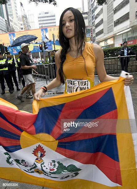 Firstyear Hong Kong University student Christina Chan Hauman holds a Tibetan flag before the start of the Beijing Olympic torch relay in Hong Kong on...