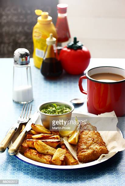 fish and chips and mushey peas on table