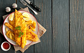 Two pieces of battered fish on a plate with chips on a wooden table with space