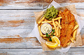 delicious crispy fish and chips - fried cod, french fries, lemon slices, tartar sauce and mashed peas on plate on paper on old wooden tabletop, authentic british recipe, view from above, blank space l