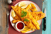 Close up of two pieces of battered fish on a plate with chips