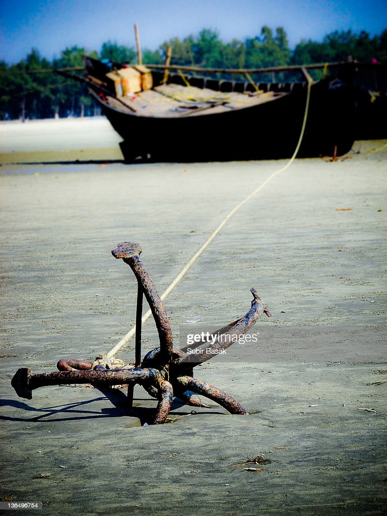 Fish boat anchored with long rope on beach stock photo for Long beach fishing boat