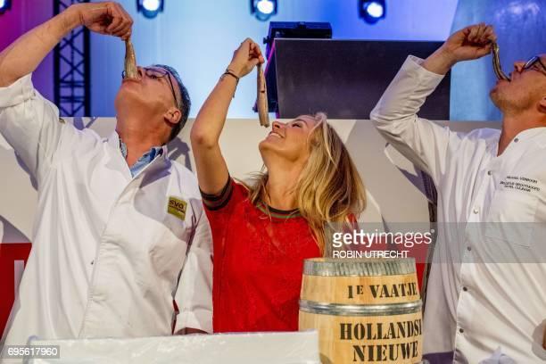 Fish educationalist Peter Koelewijn tvhost Wendy van Dijk and chef Michael Verboom taste the new herring in the harbour of Scheveningen on June 13...