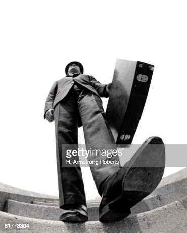Fish Eye Angle Of Salesman Walking Down Stairs Foot About To Step On Camera Briefcase Elongated Body Distortion Tall Big. : Foto de stock