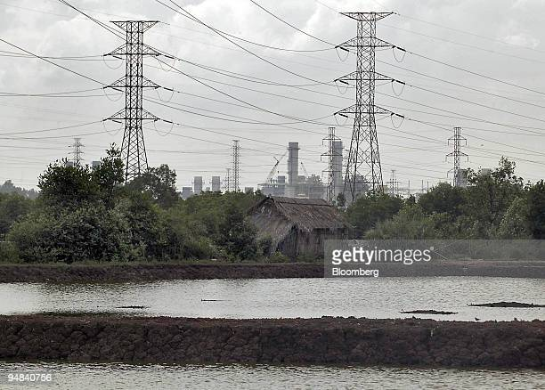 A fish farm sits under massive highvoltage pylons connected to the Phu My power complexes in Phu My just outside Saigon Vietnam December 1 2005 The...