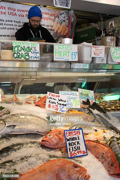 A fish monger stands behind a sales counter in front of iced salmon rock fish and trout
