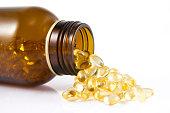 Spilled omega oil capsules on white background