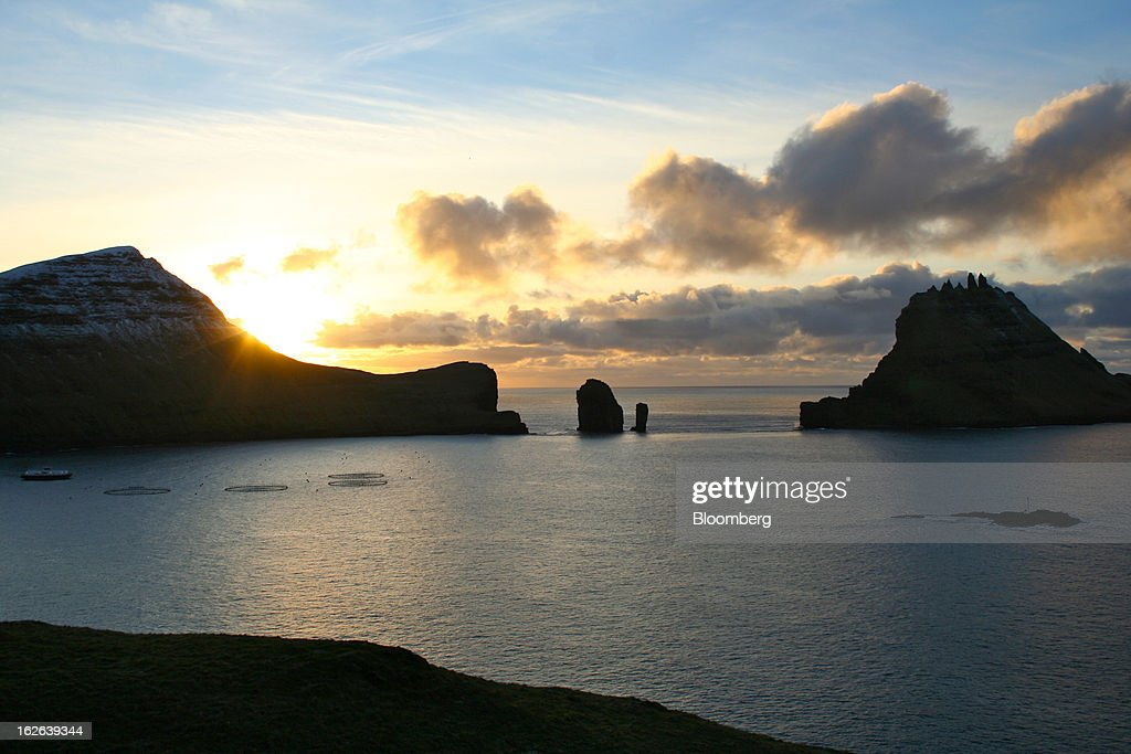 Fish pens sit in the ocean near two small islands in the western Faroe Islands, under the sovereignty of Denmark, on Friday, Dec. 7, 2012. A proposed plan would decipher the complete DNA sequence of the 50,000 citizens of this tiny, windswept land halfway between Scotland and Iceland, from its fishermen to the prime minister. Scientists already see the Faroes becoming a model for the use of human genomes. Photographer: John Lauerman/Bloomberg via Getty Images