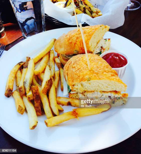Fish sandwich on a roll with french-fried potatoes outdoors