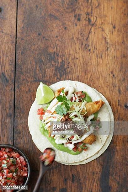Fish taco and bowl of salsa, overhead view