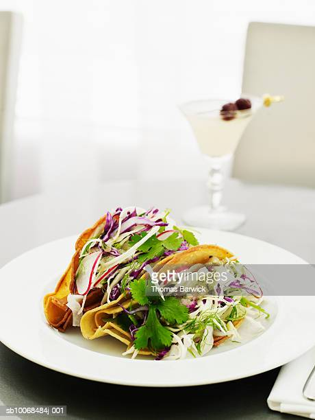 Fish tacos with cod, salsa verde, fennel and cabbage, cocktail in background