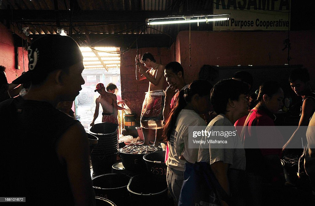 Fish vendors await for customers inside the wet market along the Coastal road on May 5, 2013 in Manila, Philippines. Around 13,000 hectares of the coastal area is to be recalimed and developed under the Public Private Partnership (PPP) of the Philippine government.