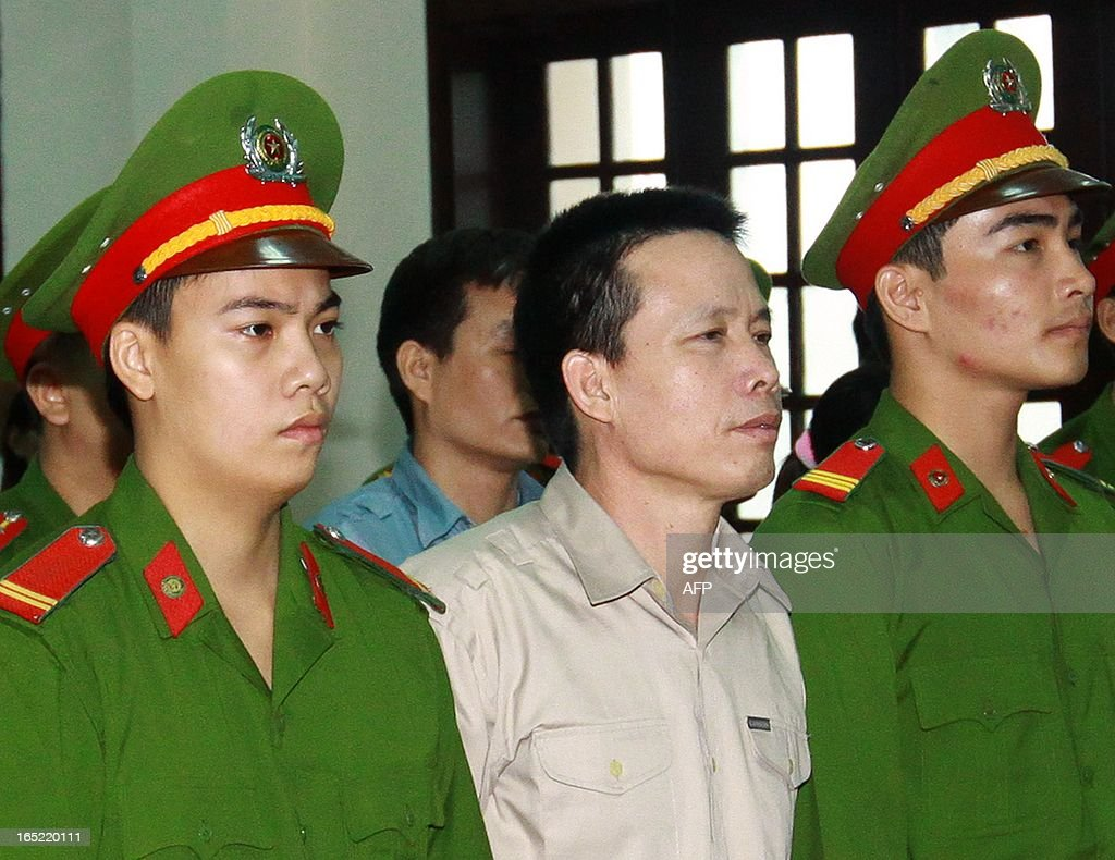 Fisher farmer Doan Van Vuon (L) is led into a courtroom as he and his family members stand trial at a local People's Court House in Northern coastal city of Hai Phong on April 2, 2013. A Vietnamese fish farmer who used a shotgun and landmines to resist forced eviction has become an instant symbol of soaring public discontent over land rights in the communist nation. AFP PHOTO/Vietnam News Agency