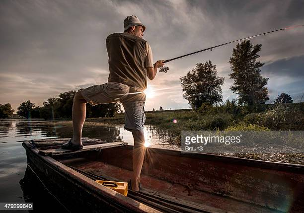 Fisherman about to cast a fishing rod from a boat.