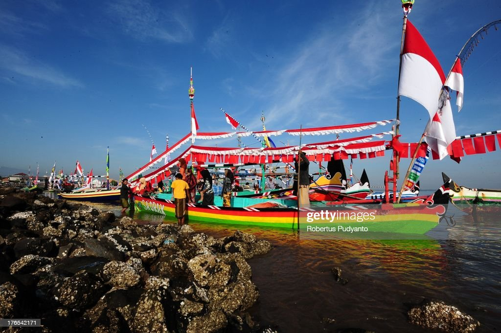 A fisherman and his family disembark a decorated boat following the Petik laut ceremony on August 15, 2013 in Lekok Beach, Pasuruan, Indonesia. Indonesian Muslims working as fishermen take part in a tradition called Petik Laut, a ceremony in which they make offerings to God and give thanks for a plentiful harvest as part of Eid celebrations.