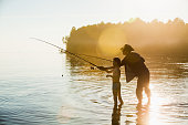 Fisherman and son at lake on sunset