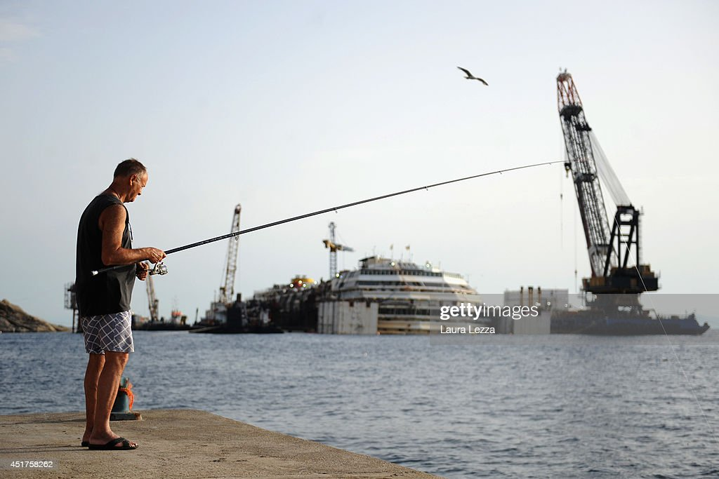 A fisherman and the sunken ship Costa Concordia are seen the day after the last sponson is installed on the port side of the wrecked ship Costa Concordia on July 4, 2014 in Isola del Giglio, Italy. A total of 30 sponsons have been attached to the Costa Concordia to re-floate the ship wreck around July 10th. The wreckage will be removed by the end of July 2014 and will be toed to the port of Genoa for dismantling.