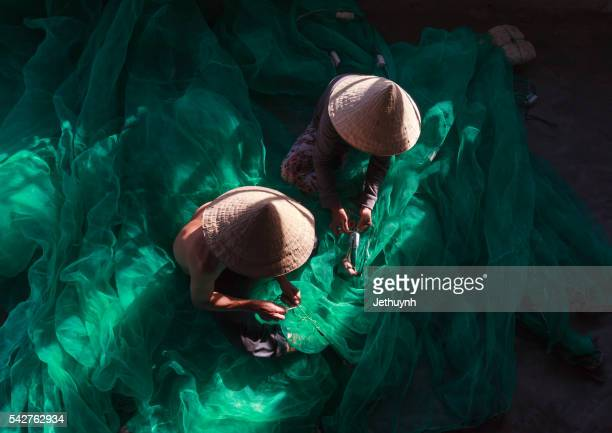 Fisherman and women with conical hat in mending fishing net