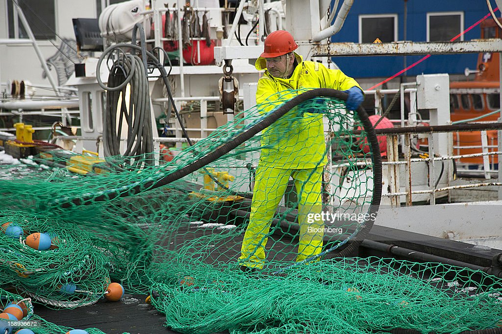 A fisherman arranges a fishing net on the quayside at the harbor in Reykjavik, Iceland, on Wednesday, Jan. 2, 2013. Iceland's inflation rate eased in December as central bank efforts to stabilize the krona with interest rate increases paid off. Photographer: Arnaldur Halldorsson/Bloomberg via Getty Images