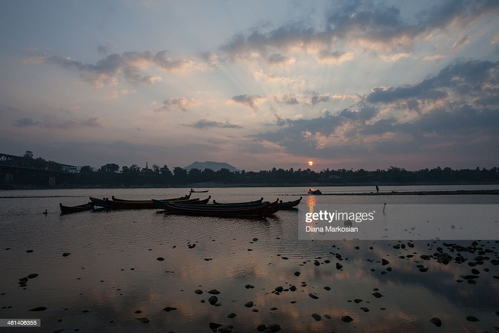 A fisherman at sunset on Irrawaddy River on December 28, 2013 in Kachin State, Myanmar. The Irrawaddy River is the lifeline of Burma, running through the center of the country. The River provides vital nutrients to wetlands and floodplain areas downstream, including the delta region which provides nearly 60 percent of Burma's rice. A massive Chinese hydropower project is under construction in the Irrawaddy river, despite fierce opposition from the Kachin Independence Organization, which broke a 17-year-ceasefire after warning that it would fight to block the project. In 2011, the hydroelectric dam project was suspended under the mandate of President U Thein Sein. The project, which involves building a 152-meter-tall hydroelectric dam at the confluence of the two rivers that form the Irrawaddy, is the brainchild of a giant Chinese state-owned firm, China Power International.