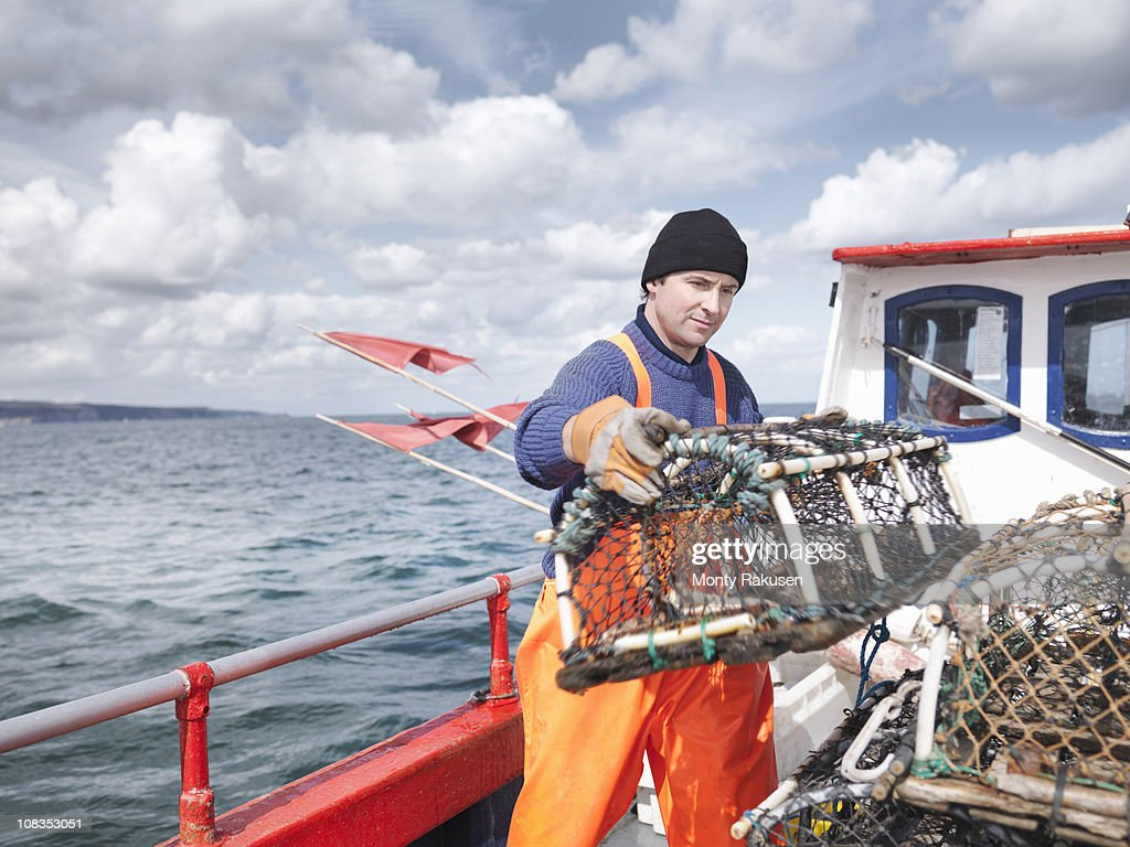 Fisherman carrying lobster pot on boat