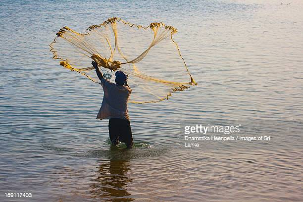 Fisherman casting a fishing net in Arugam Bay