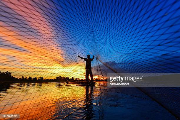 Fisherman casting fishing net at sunset, Thailand