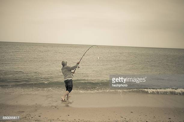 Fisherman casting fishing rod on beach, Truro, Massachusetts, Cape Cod, USA