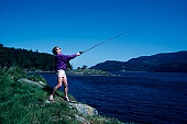 Fisherman casting into lake