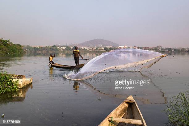 A fisherman casting net from his boat Jabi Lake in Abuja FCT Nigeria