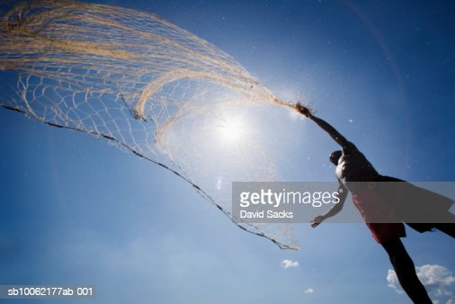 Fisherman casting net, low angle view : Stock Photo