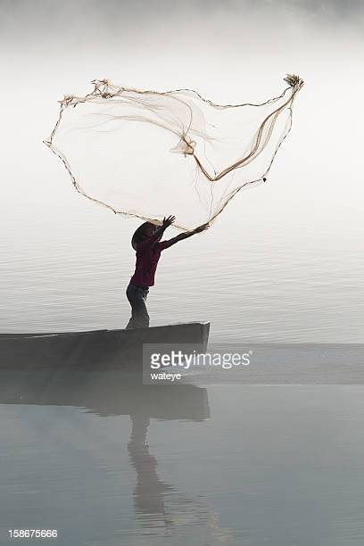 Fisherman casting net on river