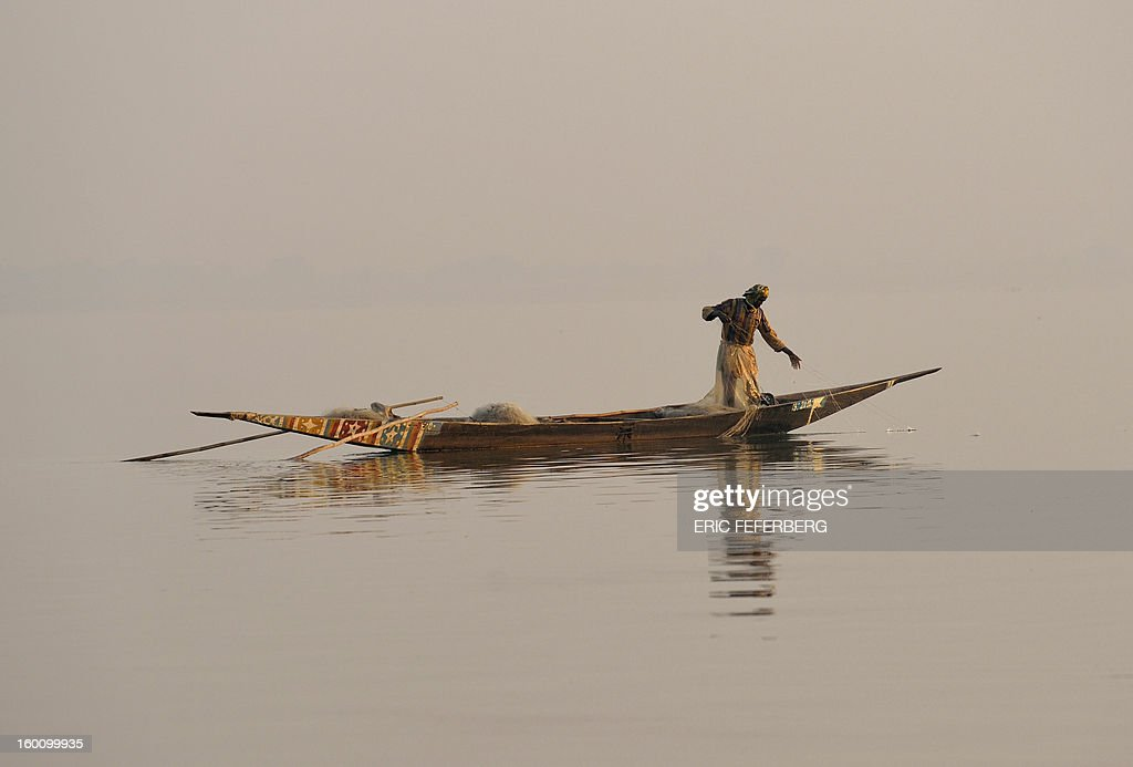 A fisherman casts his net in the Niger river on January 23, 2013 in Segou 270km north of the capital Bamako. AFP PHOTO / ERIC FEFERBERG